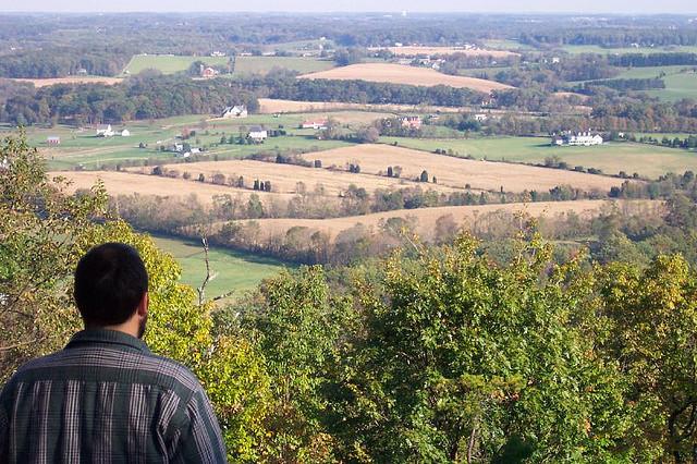 Man overlooks Maryland farmland.
