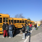 Students wait to board school buses.