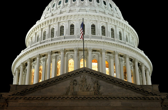 U.S. capitol at night with flag
