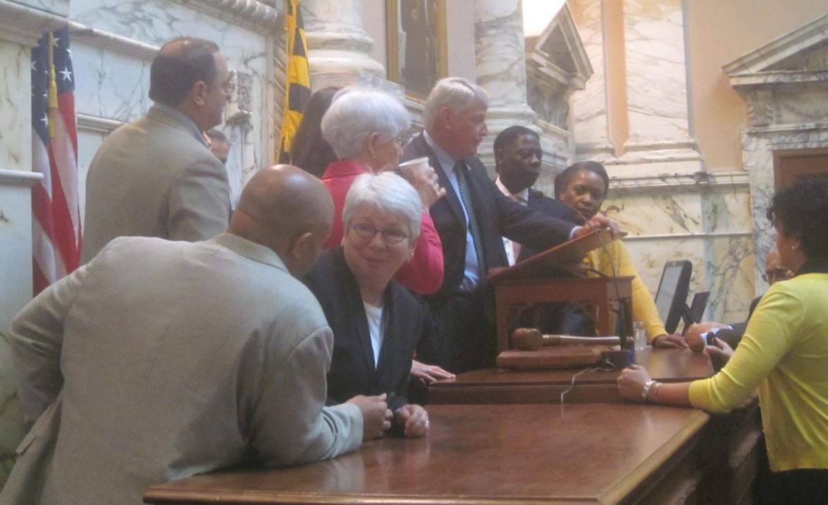 Assembly leaders confer with speaker at rostrum during special session.