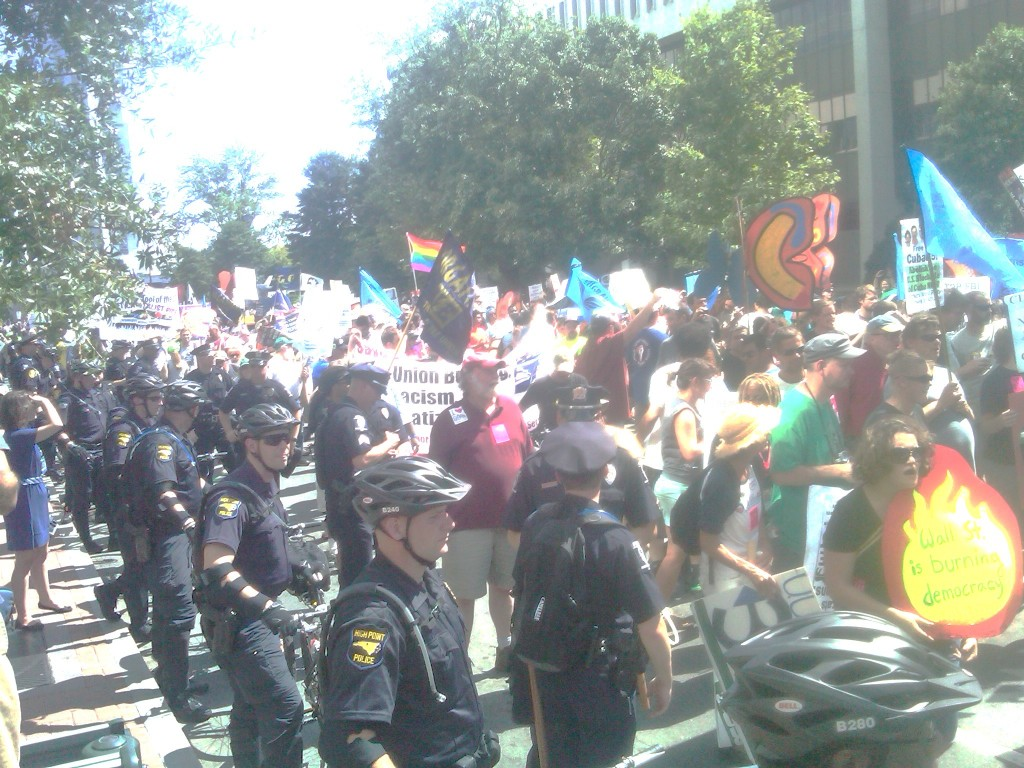 Police in bike helmets line street with parade of demonstrators.