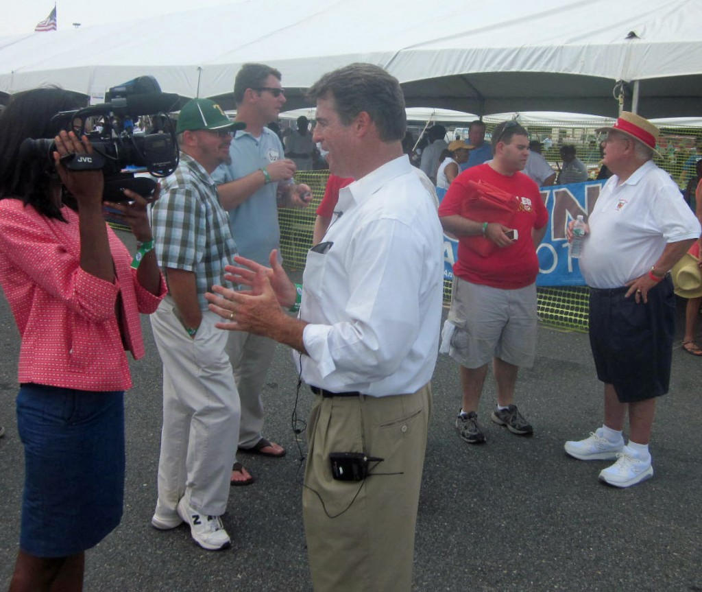 Attorney General Doug Gansler, center, an unannounced candidate for governor, talks to a TV reporter as Gansler aide Alan Brody (red shirt) talks to Del. Johnny Wood, in hat, D-St. Mary's.