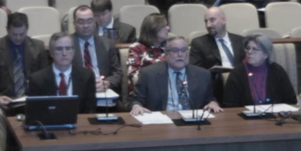 Warren Deschenaux, center at mic, surrounded by other fiscal analysts testifies on budget