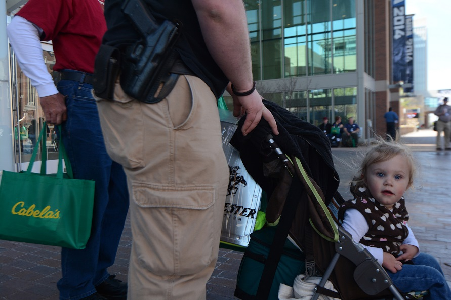 Two-year-old Aleks Gifford looks on as her mother, Kaitlynn Gifford, leaves the National Rifle Association's 143rd annual convention in Indianapolis on April 25, 2014. Photo by Jacob Byk/News21.