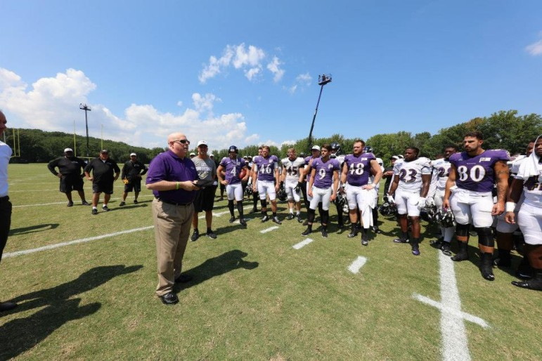 Gov. Larry Hogan talks to Ravens at training camp.