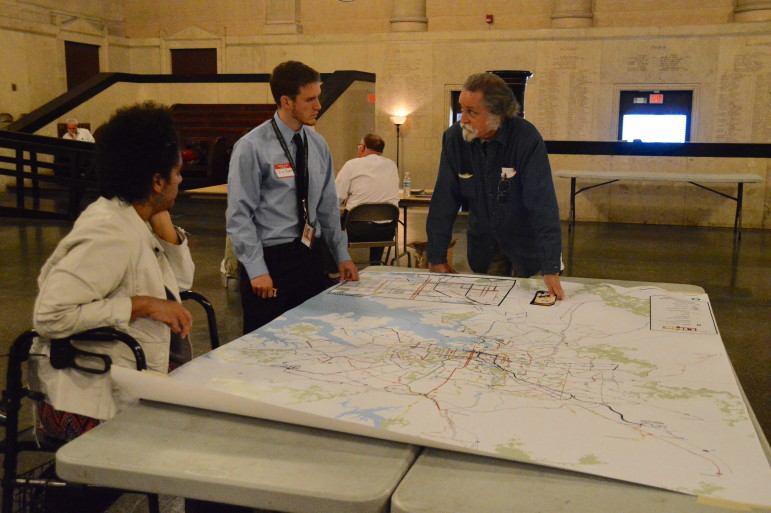 Martin French (far right) talks with Maryland Transit Administration employee Chris Snyder (middle) about bus routes at the first BaltimoreLink workshop at Baltimore's War Memorial on Nov. 4, 2015. French said that the existing bus routes are congested and need to be improved so that people can get to work on time. (Capital News Service photo by Brittany Britto)