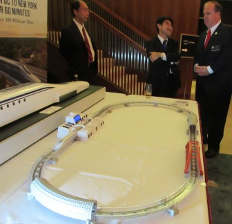Del. Bob Long of Dundalk discusses the maglev train project with Japanese representatives next to a model of the high-speed train at a reception Monday night at the home of Japan's ambassador.