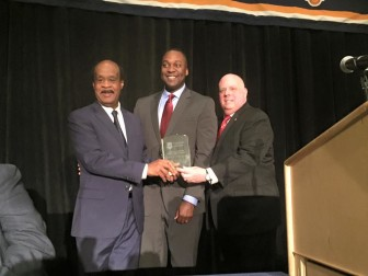Howard County Council Chairperson Calvin Ball, center, gets Marilyn Praisner Public Service Award from Gov. Larry Hogan, right, and outgoing MACo President Ike Leggett, the Montgomery County Executive.