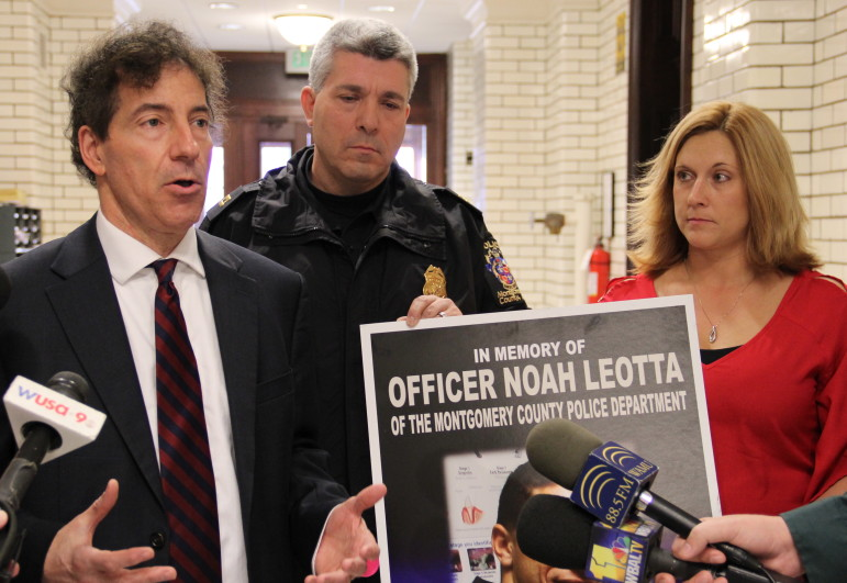 Sen. Jamie Raskin, left, stands with Captain Tom Didone of Montgomery County, and Lisa Spicknall, state program director of MADD Maryland, for a press conference at the Maryland State House Jan. 13. Didone held a poster commemorating Officer Noah Loetta, who was killed by a repeat drunk driving offender last month. Sen. Raskin and Del. Ben Kramer will be introducing a bill requiring all convicted drunk drivers to use ignition interlocks.