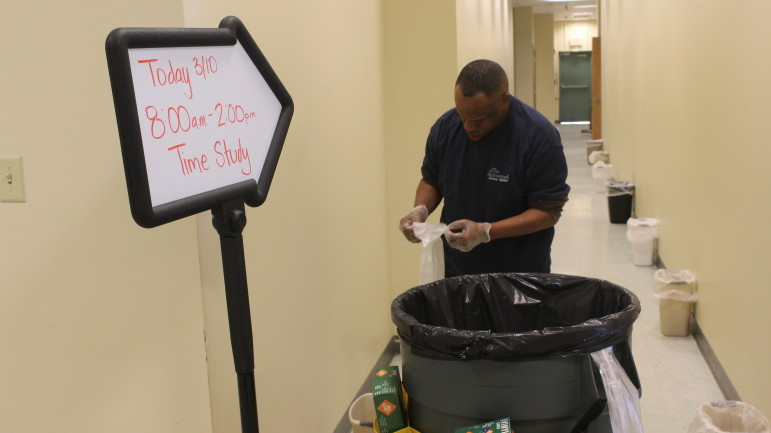 Brian Beckham, a custodial worker with disabilities at Melwood, finishes tying up the final trash bag during a demonstration of the now-obsolete time trials  in the Melwood center. Capital News Service photo by Josh Magness.