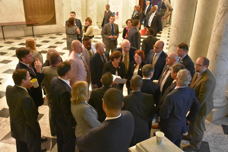 Members of House Environment and Transportation hold a quick meeting Monday night in the lobby of the State House.
