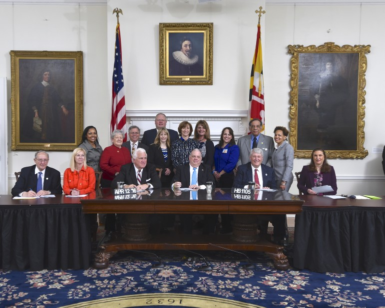 Gov. Hogan signs bill to investigate Howard County school board release of information. Behind him are legislators of both parties and school board candidates.