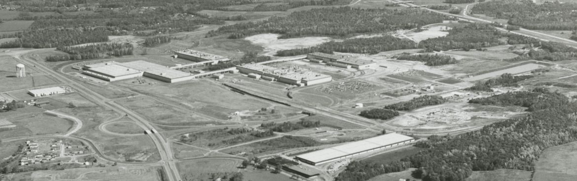 This aerial photo shows the existing water tower and Snowden River Parkway on the left, I-95 on the upper right, Snowden's intersection with Oakland Mills Road at the bottom, and General Electric's buildings in the middle. Photo for The Rouse Co. by WM. S. Pearson Jr. Courtesy of Columbia Archives.