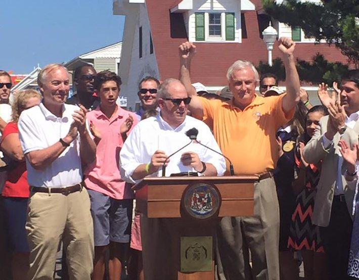 Gov. Larry Hogan signs executive order declaring schools will strart after Labor Day. He is joined by Comptroller Peter Franchot applauding on the left and Sen. Jim Mathias with arms raised on the right. Governor's Office Photo.