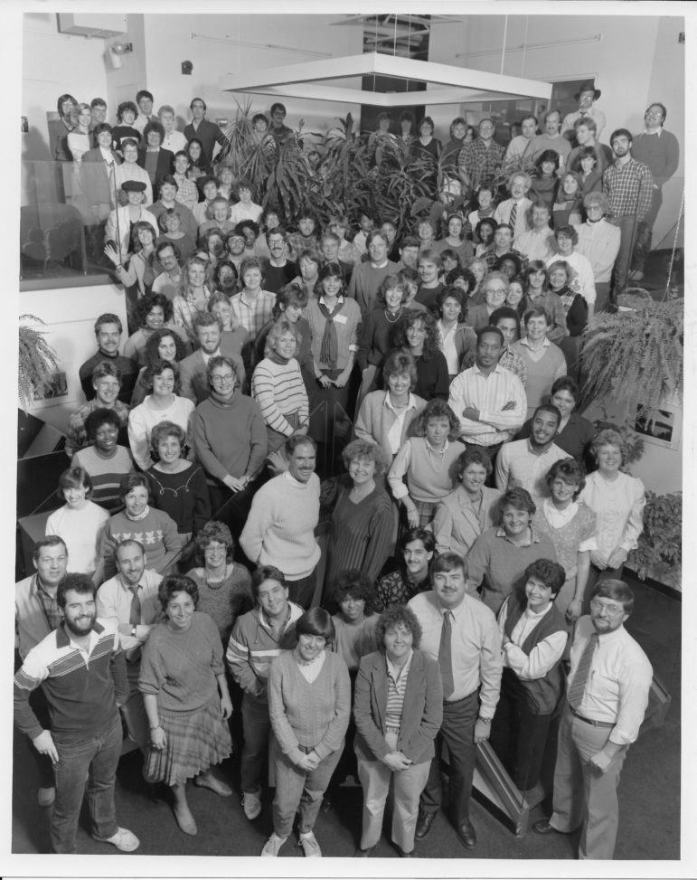 Patuxent Publishing staff, including Columbia Flier, sometime in the 1980s in the foyer of the Flier building. In the lower center are Publisher Zeke Orlinsky and General Manager Jean Moon. Editor Tom Graham is at the very bottom right; Len Lazarick is second person to his left. Photographer unknown.