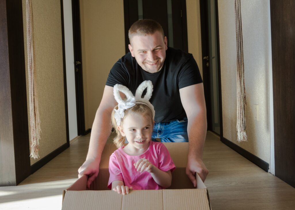 Father and daughter playing with a moving box.